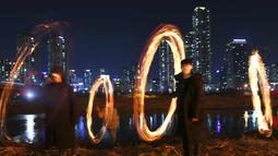 """Peserta membuat lingkaran api jelang perayaan """"Jeongwol Daeboreum"""" (Bulan Purnama) di Seoul, Korea Selatan (1/3). Permainan ini dipercaya dapat menyuburkan tanah dan menyingkirkannya hama sehingga memastikan hasil panen melimpah. (AFP Photo/Jung Yeon-je)"""
