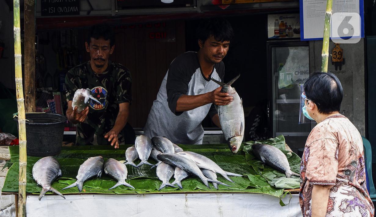 Pedagang ikan bandeng melayani pembeli di kawasan Rawa Belong, Jakarta Barat, Rabu (10/2/2021). Jelang Tahun Baru Imlek 2021, para pedagang ikan bandeng mulai bermunculan di Rawa Belong. (Liputan6.com/Johan Tallo)