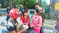 Warga beragama Hindu membagikan takjil kepada pengendara motor dan jemaah masjid di Kota Kendari, Rabu (15/5/2019). (Liputan6.com/ Ahmad Fua)