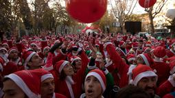 Orang-orang mengenakan kostum Sinterklas berkumpul di garis start untuk mengambil bagian dalam Santa Claus Run di Madrid, Spanyol, Minggu (9/12). Ribuan memeriahkan acara yang sudah diselenggarakan sejak 7 tahun yang lalu. (AP/Emilio Morenatti)