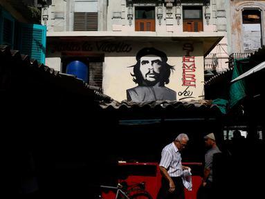 Warga beraktivitas di bawah sebuah mural pahlawan Revolusi Kuba Ernesto 'Che' Guevara yang menghadap ke pasar makanan di Havana, Kuba (28/12). Havana adalah kota terbesar di Kuba dan di seluruh Karibia. (AP Photo / Desmond Boylan)