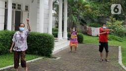 Warga yang positif covid-19 berolahraga di halaman rumah yang diubah menjadi tempat isolasi mandiri di Jalan MPR 1, Cilandak, Jakarta, Rabu (7/7/2021). Mereka yang menjalani isolasi mandiri di rumah mewah itu mendapatkan bantuan kebutuhan sehari-hari dari warga sekitar. (merdeka.com/Arie Basuki)