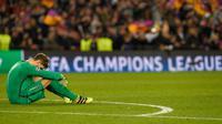 Kiper PSG, Kevin Trapp terduduk lesu usai dikalahkan Barcelona pada leg kedua babak 16 besar Liga Champions di stadion Camp Nou, Spanyol (9/3). Barcelona menang 6-1 (agregat 6-5). (AFP PHOTO / Lluis GENE)