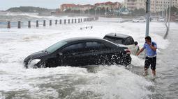 Sejumlah mobil saat dihantam ombak besar yang disebabkan Topan Yagi di sepanjang pantai laut di Qingdao di provinsi Shandong timur China, (13/8). Menurut Kantor Berita Xinhua, Topan Yagi memiliki kecepatan hingga 102 kilometer per jam. (AFP Photo)