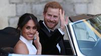 Pangeran Harry dan istrinya Meghan Markle tersenyum saat meninggalkan Kastil Windsor untuk ke acara resepsi dekat Frogmore House (19/5). Mobil yang dikenderai Pangeran Harry yaitu Jaguar Classic E-Type Concept Zero.  (AFP Photo/Pool/Steve Parsons)