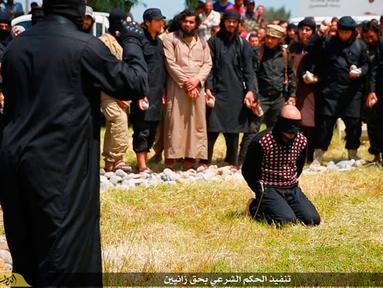 Militan ISIS mengerumuni seorang pria saat akan dieksekusi di Kota Mosul, Irak, 27 April 2015. Kelompok HAM Suriah di AS sedang mengumpulkan bukti-bukti terhadap militan ISIS yang dianggap bertanggung jawab atas teror selama empat tahun di Suriah. (Militant website via AP)