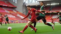 Bek Liverpool, Andrew Robertson (tengah) menjauhkan bola dari striker Aston Villa Anwar El Ghazi dalam lanjutan Premier League 2019-2020, Minggu (5/7/2020). Liverpool berhasil meraih kemenangan atas Aston Villa dengan skor 2-0. (Shaun Botterill / POOL / AFP)