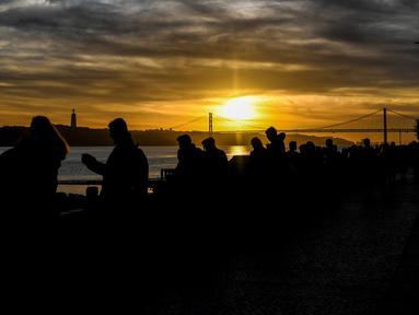 Orang-orang menikmati matahari terbenam di Ribeira das Naus di Lisbon (17/12). Lisboa atau Lisbon merupakan ibu kota  Portugal. (AFP Photo/Patricia De Melo Moreira)