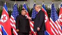 Presiden AS, Donald Trump bertemu dengan Pemimpin Korea Utara, Kim Jong-un di resor Capella, Pulau Sentosa, Singapura, Selasa (12/6). Pertemuan ini merupakan yang pertama kalinya bagi pemimpin AS dan Korut untuk bertatap muka. (SAUL LOEB/AFP)