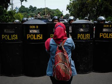 Seorang mahasiswa mengabadikan penjagaan kepolisian saat aksi demonstrasi di Istana Negara, Jakarta, Kamis (20/10). Aksi yang dilakukan mahasiswa merupakan peringatan tepat dua tahun pemerintahan Joko Widodo-Jusuf Kalla. (Liputan6.com/Faizal Fanani)