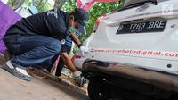 Petugas mengetes gas buang pada kegiatan uji emisi kendaraan di Taman Kota 1 BSD, Tangerang Selatan, Rabu (3/10). Dinas Lingkungan Hidup (DLH) Kota Tangerang Selatan menggelar uji emisi guna menekan angka polusi kendaraan. (Merdeka.com/Arie Basuki)