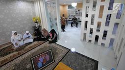 Keluarga berdoa menunggu kedatangan jenazah Kepala Pusat Data Informasi dan Humas BNPB Sutopo Purwo Nugroho di rumah duka Raffles Hils, Cimanggis, Depok, Jawa Barat, Minggu (7/7/2019). Rencananya jenazah Sutopo akan dimakamkan di Boyolali Jawa Tengah Senin (8-7-2019). (Liputan6.com/Herman Zakharia)