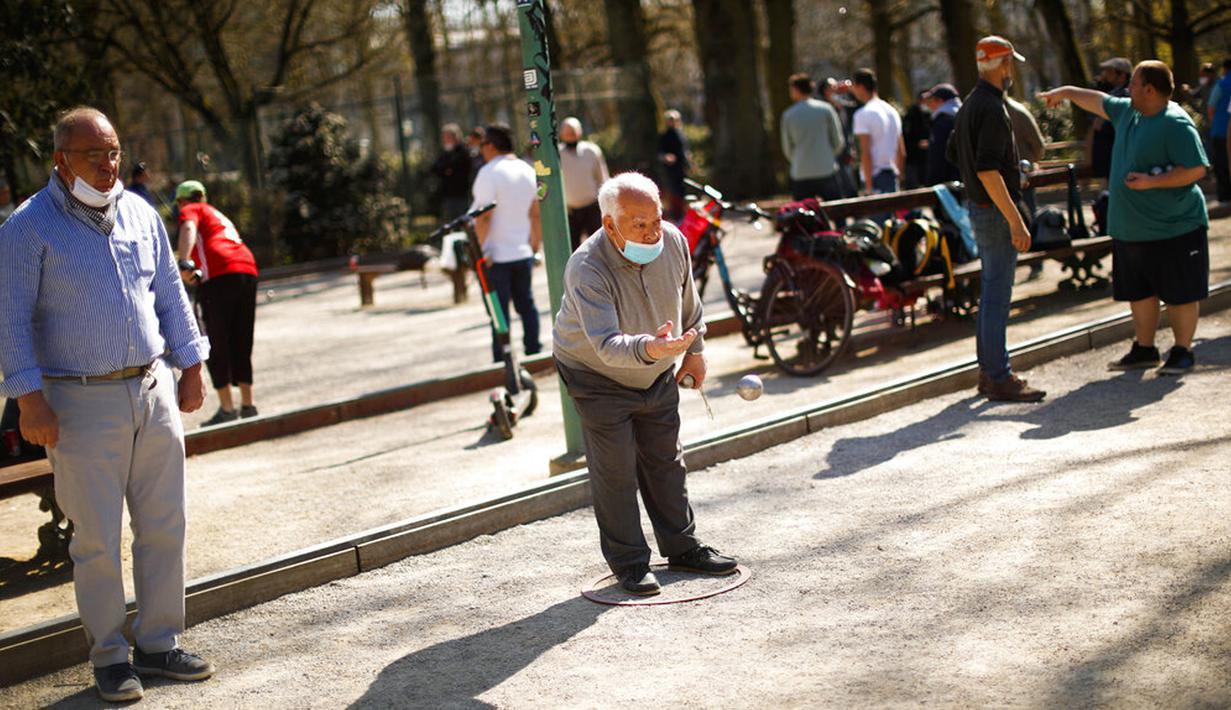 Seorang pria mengenakan masker untuk mencegah penyebaran COVID-19 saat memainkan boule di Taman Cinquantenaire, Brussel, Belgia, Senin (29/3/2021). Belgia kembali memberlakukan lockdown ketat sebagai tanggapan atas lonjakan infeksi COVID-19 yang mengkhawatirkan. (AP Photo/Francisco Seco)