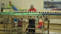 Pekerja memantau jalur produksi susu kedelai di sebuah pabrik di Nanning, Guangxi, China, Selasa (12/3). Dalam dua bulan pertama tahun ini, produksi industri China menunjukkan perlambatan stabilisasi ekonomi terbesar kedua di dunia itu. (STR/AFP)