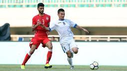 Pemain belakang Bahrain, Ahmed Bughammar (kiri) berusaha menahan laju pemain Uzbekistan, Kenjabaev Islom saat laga PSSI Anniversary Cup 2018 di Stadion Pakansari, Kab Bogor, Senin (30/4). Laga berakhir imbang 3-3. (Liputan6.com/Helmi Fithriansyah)
