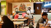 Karyawan melayani pengunjung di restoran yang berada di Mal Central Park, Jakarta, Jumat (20/8/2021). Restoran dalam pusat perbelanjaan kini bisa makan di tempat dengan syarat kapasitas maksimal 25 persen, satu meja maksimal dua orang, dan waktu makan maksimal 30 menit. (Liputan6.com/Angga Yuniar)
