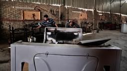 Mekanik merakit minicars yang merupakan produk lokal Mesir di sebuah bengkel di Kerdasa, Kairo, Mesir (1/8). (AP Photo/Nariman El-Mofty)