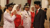 Gubernur Riau Syamsuar (kiri) memberi salam kepada Presiden Joko Widodo atau Jokowi saat pelantikan di Istana Negara, Jakarta, Rabu (20/2). Syamsuar dilantik menjadi Gubernur Riau periode 2019-2024. (Liputan6.com/Angga Yuniar)