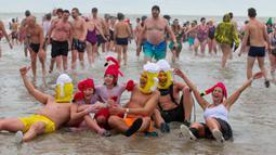 Orang-orang dengan kostum warna-warni menyerbu perairan Laut Utara  untuk merayakan akhir pekan pertama Januari 2020 di Ostend, Belgia, Sabtu (4/1/2020). Cuaca dingin tak menghalangi mereka untuk menceburkan diri ke laut yang merupakan salah satu tradisi tahun baru.  (NICOLAS MAETERLINCK/BELGA/AFP)