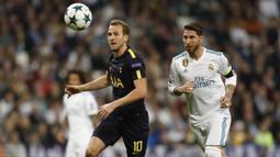 Striker Tottenham, Harry Kane, beradu cepat dengan bek Real Madrid, Sergio Ramos, pada laga Liga Champions di Stadion Santiago Bernabeu, Madrid, Selasa (17/10/2017). Kedua klub bermain imbang 1-1. (AP/Fransisco Seco)