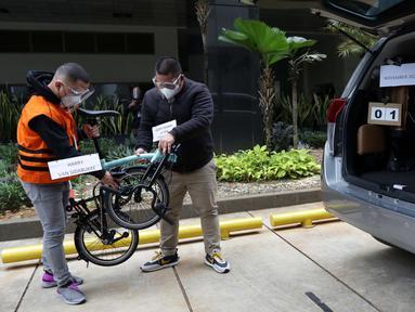 Tersangka Harry van Sidabuke (kiri) menyerahkan sepeda Brompton kepada perantara anggota Komisi II DPR Ihsan Yunus, Agustri Yogasmara saat rekonstruksi perkara dugaan korupsi pengadaan bantuan sosial penanganan COVID-19 di gedung KPK, Jakarta, Rabu (10/2/2021). (Liputan6.com/Helmi Fithriansyah)