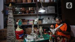 Sugito (68) menyelesaikan pembuatan miniatur Monas dari kertas koran bekas di Bank Sampah Tri Alam Lestari, Jakarta Selatan, Rabu (9/6/2021). Selain miniatur Monas, Sugito juga memanfaatkan kertas bekas untuk membuat berbagai macam barang kerajinan yang bernilai ekonomis. (Liputan6.com/Johan Tallo)