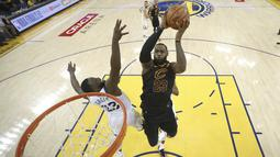 Pemain Cavaliers, LeBron James (kanan) mencoba mencetak poin saat diadang pemain Warriors, Draymond Green pada gim pertama final NBA basketball di Oakland, California, (31/5/2018). Warriors menang 124-114. (Ezra Shaw/Pool Photo via AP)