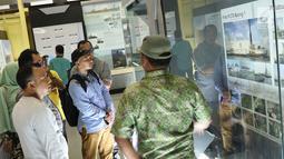 Pengunjung membaca informasi saat berkeliling Monumen Kapal Pembangkit Listrik Tenaga Diesel (PLTD) Apung 1 di Aceh, Selasa (31/7). Kapal berbobot mati 2.600 ton tersebut memiliki panjang 63 meter. (Liputan6.com/Immanuel Antonius)