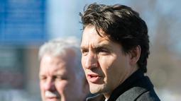 PM Kanada, Justin Trudeau menghadiri pemakaman tiga dari enam korban penembakan di Masjid Quebec di Montreal Olympic, Kamis (2/2). PM Kanada bersama ribuan warga ikut menunjukkan rasa berkabungnya di pemakaman. (Graham Hughes/The Canadian Press via AP)
