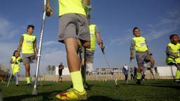 Anak-anak Palestina yang diamputasi melakukan pemanasan saat berlatih sepak bola di lapangan bermain al-Durra di kota Dier al-Balah, Jalur Gaza tengah (18/10/2019). Tim ini diawasi oleh pelatih Irlandia yang diamputasi Simon Baker.  (AP Photo/Hatem Moussa)