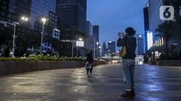 Warga berfoto di Jalan Jenderal Sudirman, Jakarta, Sabtu (26/9/2020). Berdasarkan data pemerintah, jumlah kasus kumulatif positif COVID-19 hingga Sabtu (26/9/2020) mencapai 271.339 dan Jakarta kembali jadi provinsi penambahan kasus Covid-19 tertinggi. (Liputan6.com/Johan Tallo)