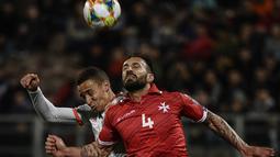 Duel udara dilakukan Steve Borg dan penyerang Spanyol. Rodrigo pada laga kedua Kualifikasi Piala Eropa 2020 yang berlangsung di Stadion Ta Qali, Malta, Rabu (27/3). Spanyol menang 2-0 atas Malta. (AFP/Filippo Monteforte)