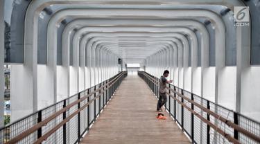 Pekerja berdiri di jembatan penyeberangan orang (JPO) Bundaran Senayan, Jakarta, Senin (21/1). JPO Bundaran Senayan telah berdiri kokoh disertai konstruksi yang lengkap terpasang. (Liputan6.com/Faizal Fanani)