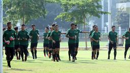 Pemain Timnas Indonesia U-19 berlari kecil jelang latihan di Lapangan B Kompleks GBK, Jakarta, Selasa (18/9). Latihan ini persiapan  PSSI Anniversary Cup U-19 dan Piala AFC U19. (Liputan6.com/Helmi Fithriansyah)
