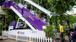 Orang-orang menaiki garbarata, yang biasanya digunakan Ppenumpang untuk naik pesawat, di restoran pop-up bertema kabin pesawat di kantor pusat Thai Airways di Bangkok, 10 September 2020. Restoran ini akan terus buka di Kantor Pusat Thai Airways setiap Rabu hingga Jumat. (Mladen ANTONOV/AFP)