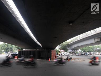 Kendaraan melintas di dekat lokasi tergulingnya truk kontainer di kolong flyover Tomang, Jakarta, Kamis (28/6). Truk kontainer bernomor polisi BN 4706 BP tersebut terguling saat hendak berbelok arah ke Jalan Tomang Raya. (Merdeka.com/Iqbal S. Nugroho)