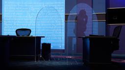 Kru produksi berjalan di belakang pembatas kaca plexiglass di atas panggung yang akan berfungsi sebagai penghalang untuk mengurangi resiko penyebaran COVID-19 saat persiapan untuk debat calon wakil presiden AS di Universitas Utah, Salt Lake City, Selasa (6/10/2020). (AP Photo/Julio Cortez)