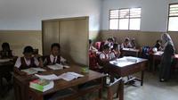 Siswa SDN 4 Kedoyo Tulungagung, Jawa Timur, berbagi ruang belajar dengan papan (Liputan6.com/Zainul Arifin)
