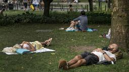 Sejumlah warga beristirahat di tempat teduh saat siang hari yang panas di Washington Square Park di New York City (17/7/2019). Gelombang panas besar akan mempengaruhi hampir dua pertiga dari Amerika Serikat, dengan Pantai Timur dan Midwest. (AFP Photo/Drew Angerer)