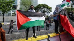 Pengunjuk rasa membentangkan bendera Palestina di depan Kedubes Amerika Serikat, Jumat (21/5/2021). Aksi yang diikuti berbagai elemen masyarakat dan ormas itu mengutuk serangan Israel dan mengajak masyarakat Indonesia untuk mendukung dan membantu Palestina. (Liputan6.com/Faizal Fanani)