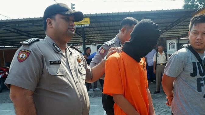 Ketua geng motor KOK digiring polisi dengan dugaan pembunuhan di depan Hotel Holiday Pekanbaru. (Liputan6.com/M Syukur)