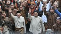 Pasangan capres dan cawapres Prabowo Subianto-Sandiaga Uno menaiki bersama pendukungnya menunjukkan salam dua jari saat mengikuti pawai Deklarasi Kampanye Damai di Monas, Minggu (23/9). (Merdeka.com/Iqbal Nugroho)