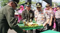 Kapolres Kebumen AKBP Rudy Kurniawan menyerahkan kue ulang tahun kepada jajaran Kodim 0709 Kebumen pada HUT ke-74 TNI. (Foto: Liputan6.com/Polres KebumenMuhamad Ridlo)