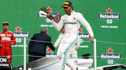 Pembalap Mercedes Lewis Hamilton berselebrasi membawa pialanya setelah berhasil menjuarai balapan GP Meksiko di Autodromo Hermanos Rodriguez, Mexico City (28/10/2019). Hamilton unggul 74 poin atas Bottas di posisi kedua klasemen dengan 289 poin. (AP Photo/Eduardo Verdugo)
