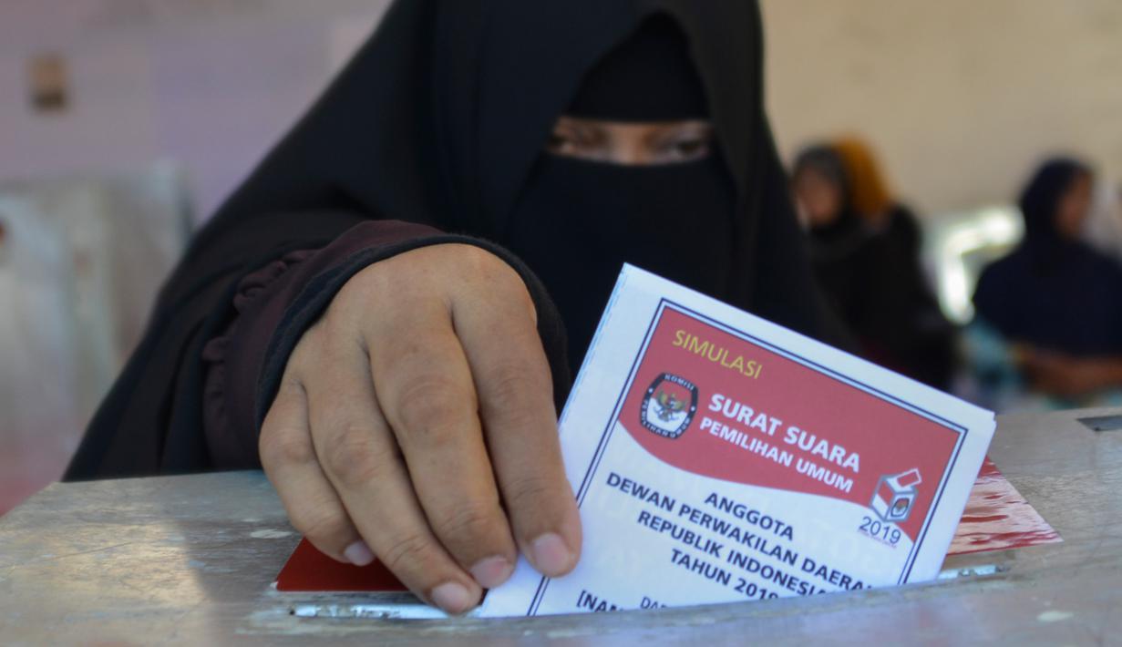 Seorang wanita memasukan kertas suaranya saat latihan pra-pemilihan di Banda Aceh, provinsi Aceh (6/4). Indonesia akan menyelenggarakan Pemilu serentak pada 17 April 2019. (AFP Photo/Chaideer Mahyudin)