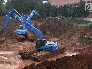 Pekerja menggunakan alat berat saat menyelesaikan pembuatan Waduk Kampung Rambutan, Jakarta, Kamis (26/4). Pemprov DKI Jakarta kembali melanjutkan proyek waduk seluas 12 hektare tersebut. (Merdeka.com/Iqbal Nugroho)