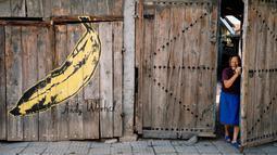 Seorang wanita keluar dari rumah yang dindingnya berhias lukisan mural bergambar pisang karya Andy Warhol di desa Staro Zhelezare di Bulgaria, 4 Agustus 2018. Para seniman mewarnai desa ini dengan mural outdoor besar yang berwarna. (AFP/Dimitar DILKOFF)