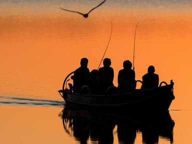 Nelayan lokal mengayuh perahu saat matahari terbenam di danau Lusiai dekat kota kecil Ignalina, sekitar 120 km (74,5 mil) utara ibukota Vilnius, Lithuania (3/6/2019). (AP Photo/Mindaugas Kulbis)