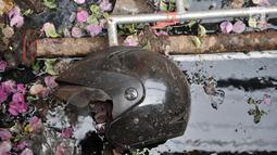 Sebuan helm terlihat berada di selokan depan Gedung Pos Polisi Subsektor Palmerah, Jakarta, Rabu (25/9/2019). Aksi pembakaran oleh amukan demonstran tersebut menghanguskan hampir seluruh bagian gedung pos polisi, sepeda motor serta barang-barang di dalamnya. (merdeka.com/Iqbal S. Nugroho)