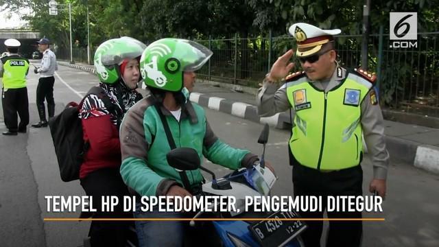 Petugas polisi Polres Jakarta Timur menegur sejumlah pengemudi ojek online yang menggunakan HP saat berkendara. Petugas mengimbau pengemudi ojek online untuk tidak menaruh HP di speedometer atau stang pada kendaraan.